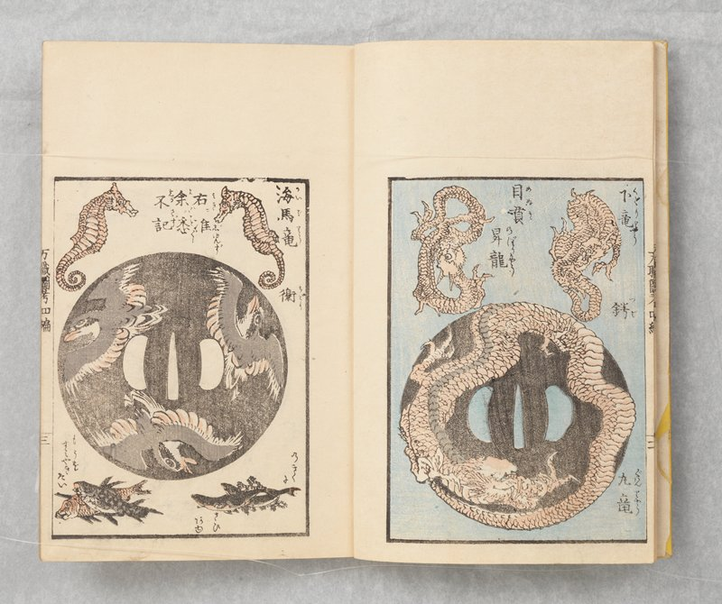 yellow cover; color images of tsuba designs, turtles, cranes, dragons, landscapes; other round designs of shells, people in boats, fish; other images of women, warriors, demons; flowers, plants