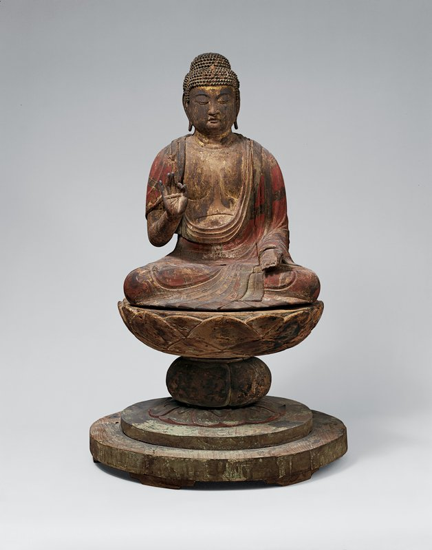 seated Buddha; PL hand in lap with open palm, index and thumb loosely touching; PR hand up, with index finger and thumb touching; two-tiered knobby hair, long earlobes; traces of red pigment on robes; seated on wide, stylized lotus on round base