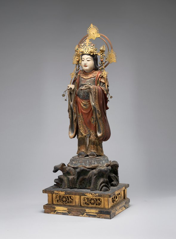 standing figure with both hands outstretched with palms up; figure wears brass crown decorated with phoenixes and adorned with glass beads, trailing down over shoulders; round metal halo on back with flaming Buddhist jewels