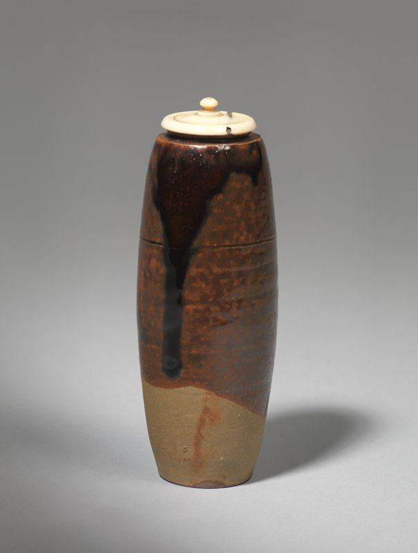 tall, narrow caddy with short, outward-curving mouth and incised line around the middle of the body; dark-brown glaze applied over a brown underglaze; bottommost portion unglazed; tiny ivory lid with concentric, incised lines