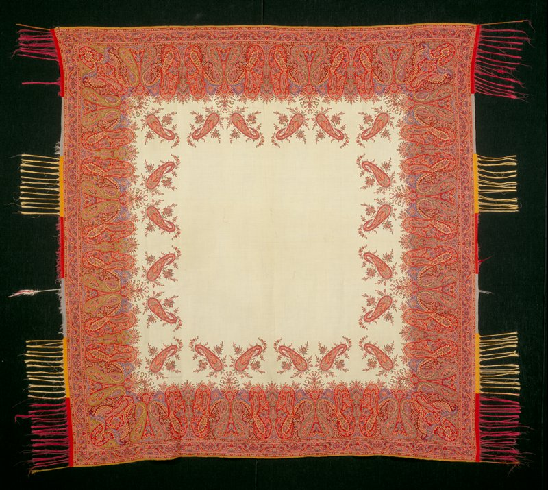 paisley shawl, silk and wool, cream colored center with border in reds, blues and greens, fringed.