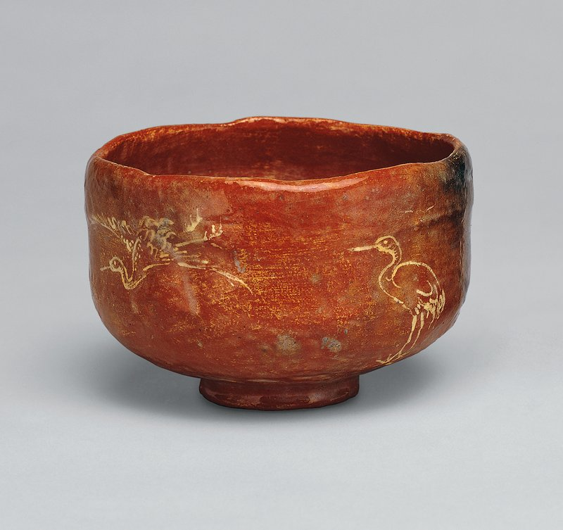 one of a pair of raku ware tea bowls; red raku bowl with incised crane design, filled with white slip; two flying cranes and one standing crane