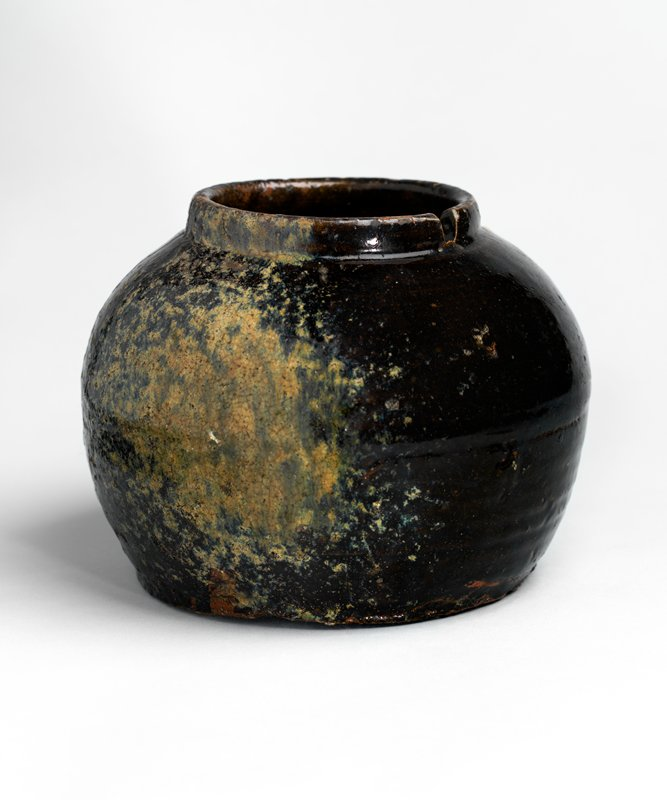 globular jar with short neck and slot for handle; wide mouth; broad, flat base; dark, almost black glaze with patch of ochre coloring on side