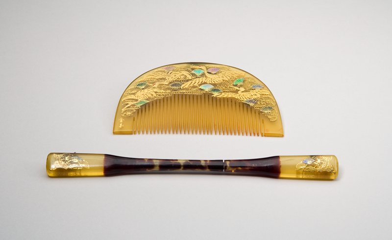hairpin with dark tortoise shell center, and lighter yellow on each side; crane on both sides with stylized pine boughs that resemble fans