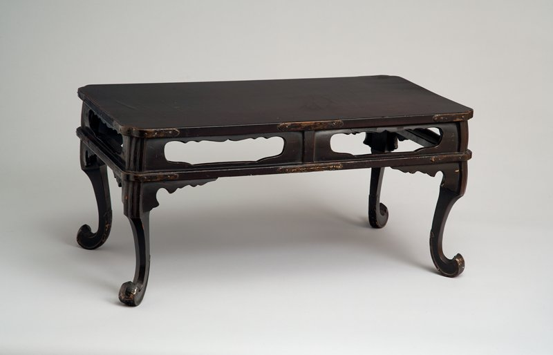 black lacquer table; scalloped cutouts on sides between base and rim; curved, scrolling, upturned feet