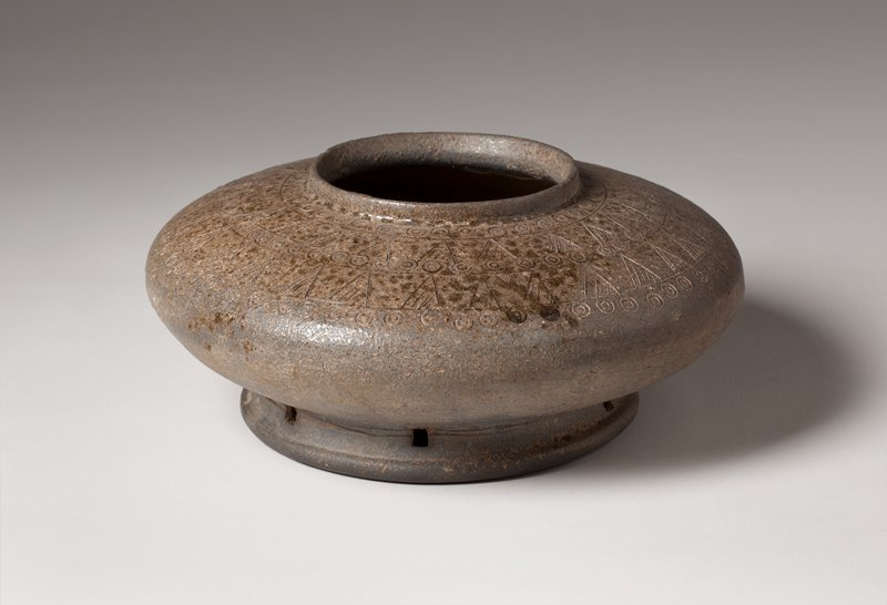 stoneware jar with brownish ash glaze evenly distributed, mostly on the upper shoulder; wide, low shape with wide mouth and short, straight lip; foot pierced in five places with small rectangular openings; five band design around upper shoulder with alternating motifs of concentric circles and triangles with cross-hatching; bands separated by incised lines