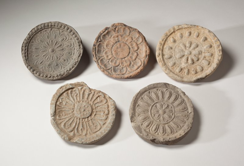 round roof tile end with impressed flower design; raised center with small spots; outlined petals of flower with vertical stems inside