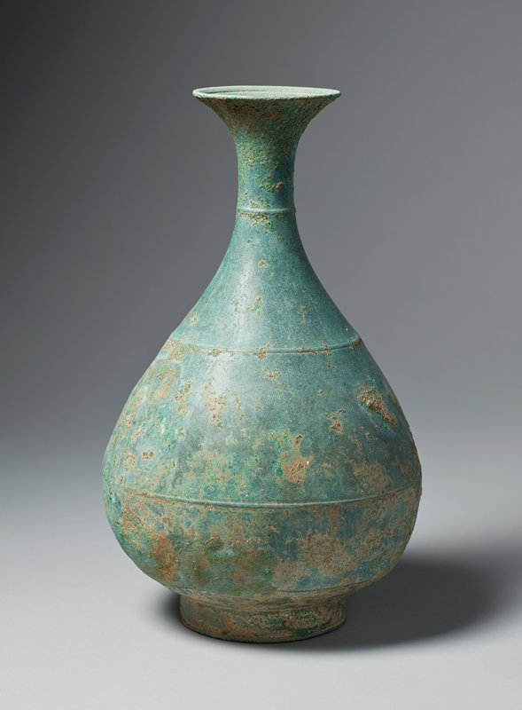 bronze bottle with swelling body, narrow neck, flared mouth; three shallow ribs encircling bottle over body, shoulder, and neck; incised line inside mouth; short foot; green from patina