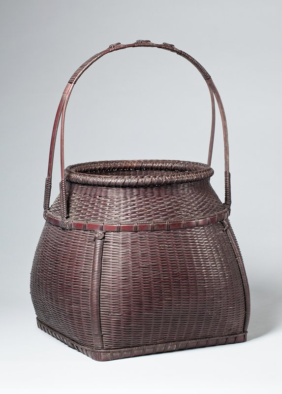 woven bamboo basket in cherry finish with oval opening and a body decorated with four vertical strips emanating from circular design just below a band of bamboo encircling entire basket; two strips of bamboo merge into one rounded arch with three decorative knots on top; body of basket is round, but the underside forms a square; on the underside are four thick strips of bamboo woven to form a square, and one of the strips has an etched stamp
