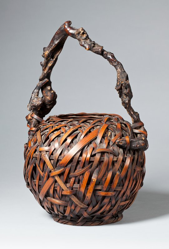 unsigned; small, round basket with crisscrossing closed weave; handle made of twisted, gnarled branch that comes to a point near center
