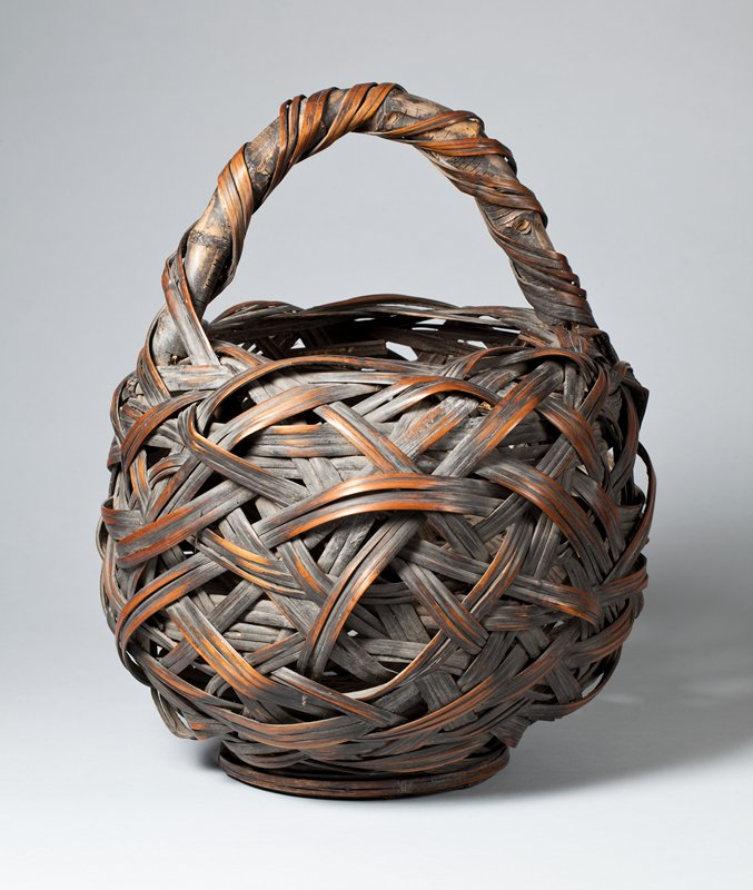 large round basket made of crisscrossing weave of three strands each of bamboo; short, fat wooden handle of strips wound loosely around a thick bent stick