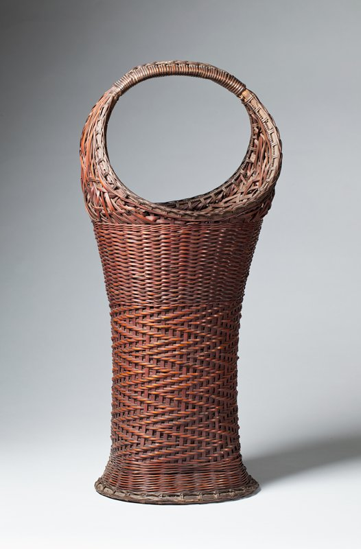 tall, narrow basket that flares upward into circular form at top, forming handle; slightly flared round base with squared edges just above foot; closed weave; zigzagging weave pattern down most of body, with plain horizontal weave pattern near top; looping pattern up around round handle; comes with bamboo cylinder insert