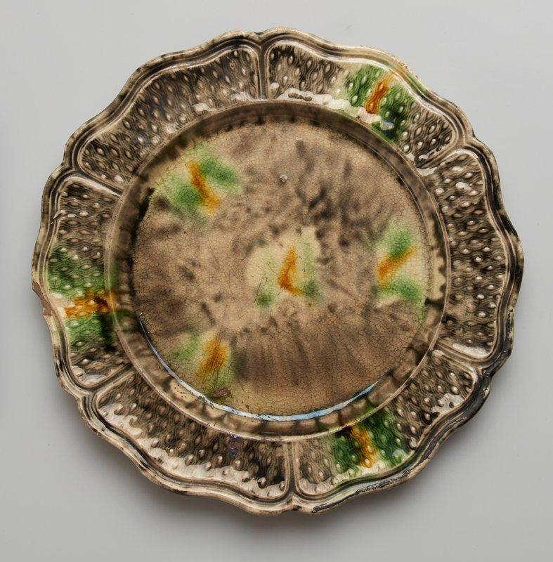 Plate, small, with depressed center and shaped edge. Flat rim decorated with wavy lines and small oval bosses. Grey green and yellow glaze. ceramic
