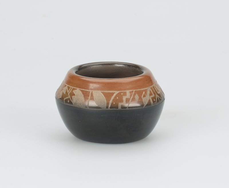 small pot; lower half: gloss black, upper half: burnt sienna; geometric pattern incised in band; interior: matte brown