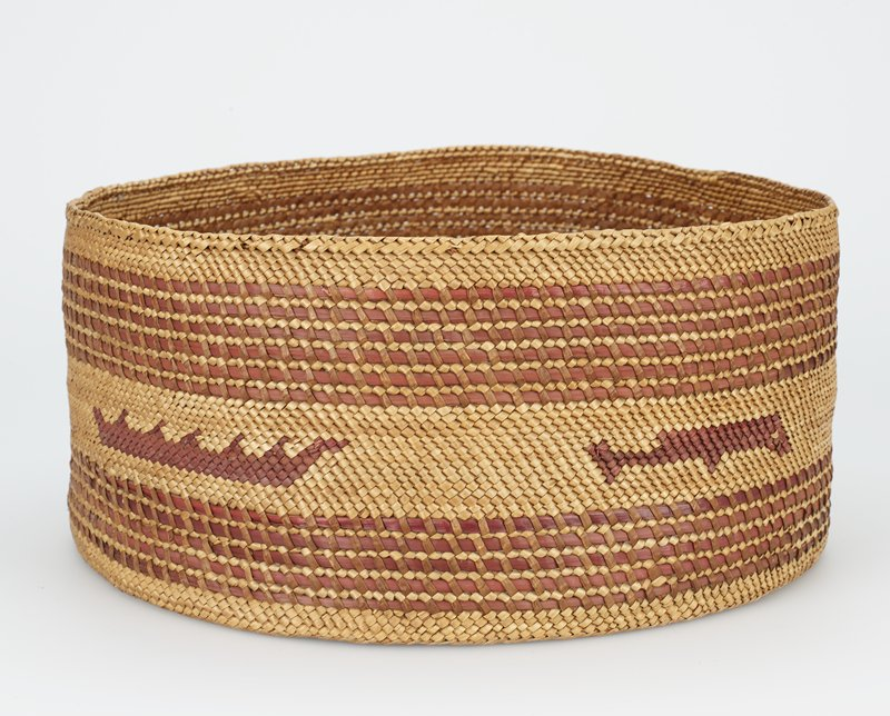 squat, cylindrical basket; primary fibers tan with brownish/red bands in 2 alternating sections near foot and lip; central tan band has 2 ducks, 1 fish and 2 crown motifs