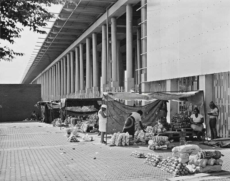 black and white photograph of street venders selling produce in front of a modern building with a colonnade