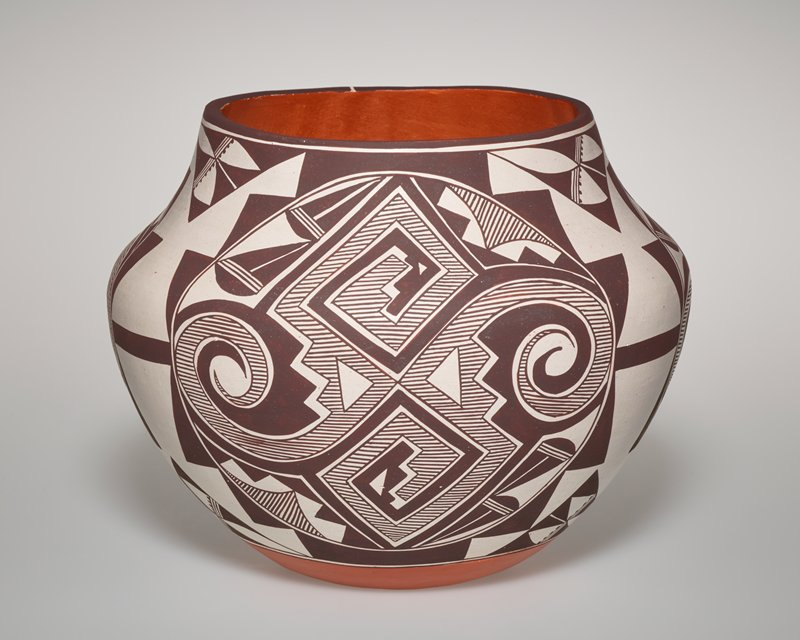 white ground with four central pattern vinettes in dark brown; terra cotta on foot and inside mouth; central pattern with two square swirls vertically and one rounded swirl on each side; step pattern around exterior