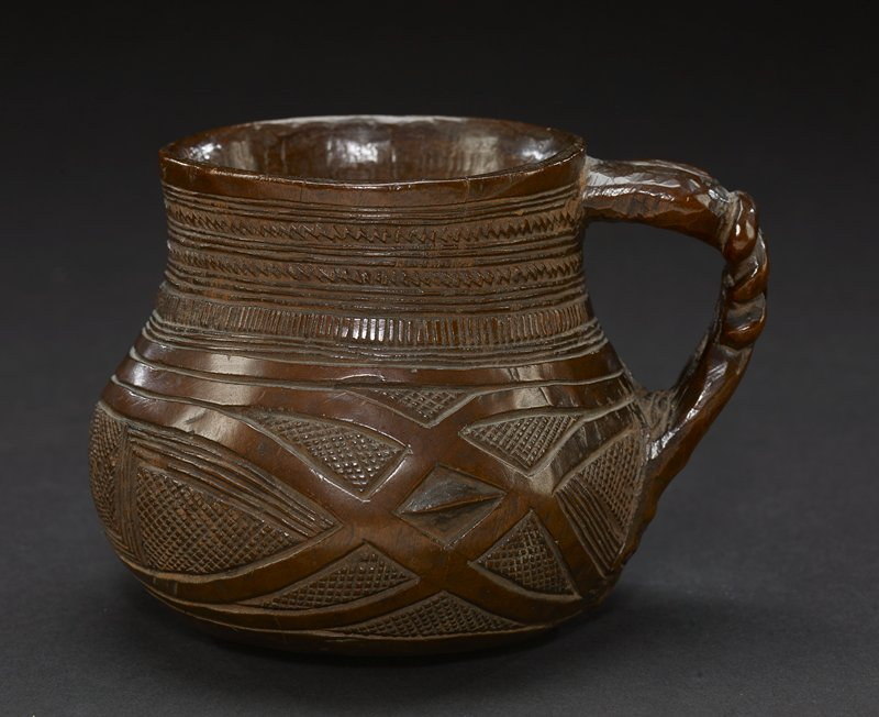 cup and handle appearing in form of hand and arm; cup has cylindrical top that rests on round bottom; top has carved patterns of zigzags in narrow rows; bottom has design with thick crisscrossed lines; handle is woven design and the part that connects to cup is a hand with four fingers; the top of the hand has a design carved into it; the piece is a dark brown hue