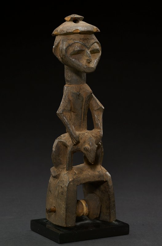 male figurative heddle pulley carved from a medium-brown wood; figure crouches on a hollow stand that holds a pulley system; figure's head is flat, eyes are oval, nose is pointed, and mouth is small and juts out from face; figure has one continuous eyebrow; at top of head is a flat round headdress with a small flat ball at center top; a line runs down the center of the figure's chest and his arms are angular, slightly bent; figure's hands are slightly defined, and his feet are less so; at center in between figure's legs is an animal head that may also be read as a penis