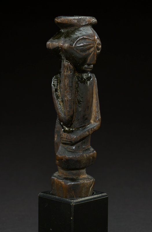 small carved staff finial representing a figure with round head, large, oval eyes, and heavy eyelids; nose is an elongated triangle, and mouth is small and lips are partly open; on top of head there is a round, flat headdress; figure has one arm around its waist with the other arm bent and the face resting on the hand of bent arm; main body of figure is cylindrical with a carved band below the waist and below that a larger, carved base; the figure is the dark brown hue of the wood from which it is carved