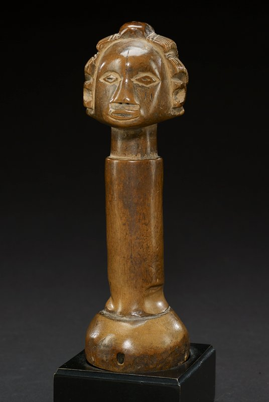 pestle body is a cylinder that spreads into a wider base; top of pestle is carved into the likeness of a head, with hair carved into five patterned rows that pull back from forehead and one patterned row running horizontally along base of neck; eyes are in the shape of diamonds and nose is in shape of flat triangle; the mouth is a thin oval with slightly parted lips; there are two, short vertical lines carved into each cheek, and a longer line running from the bridge of the nose to the middle of the forehead; the neck is slightly thinner than the body of the pestle, and a carved ring separates the body from the round base; the entire piece is a medium brown--the natural color of the wood