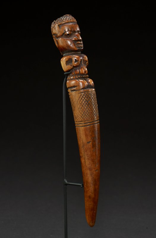 at the top of tapper is a large, square head with a face characterized by oval, wide-set eyes, prominent nose, and partially open mouth; on top of head is a small headdress carved with patterned lines and slightly rounded at top; figure kneels on cone shape of tapper--her arms are bent at her waist and she cups her breasts with her hands; figure's belly is round with a large belly button and belt at her waist; top of tapper cone has a band of hash-mark-like carvings; tapper curves down to a point; tan in color overall