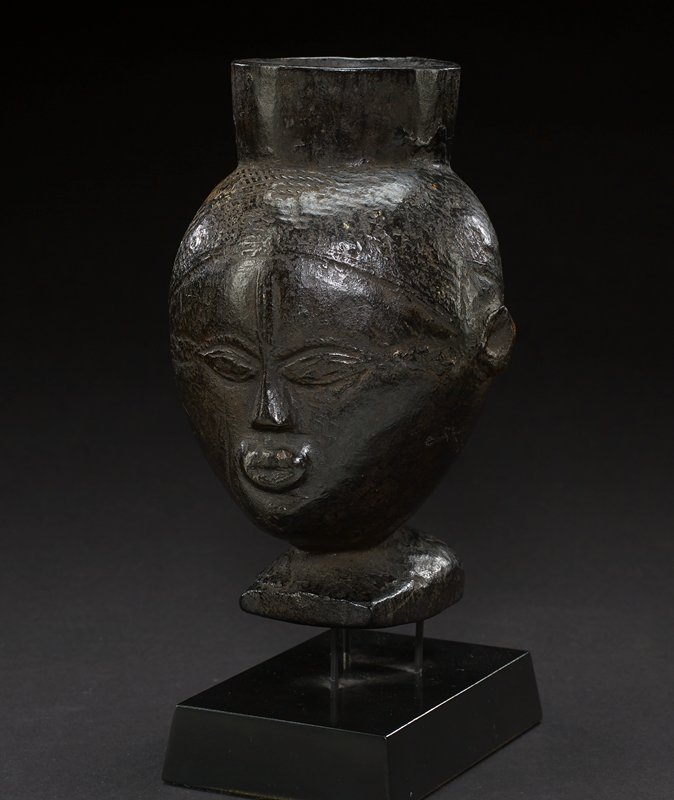 cup with carved human face; top of cup is straight and tapers into the head where carved straight lines indicate hair; face has pointed ellipses for eyes, a triangular nose, and pursed lips; there is a prominent vertical element carved between the eyes; ears at each side of head appear like slightly protruding circles with hole at center; handle of cup starts at top of head, at back, and ends at bottom of head; head tapers into a neck, which forms the base of the cup; entire piece is carved from wood with dark-brown hue