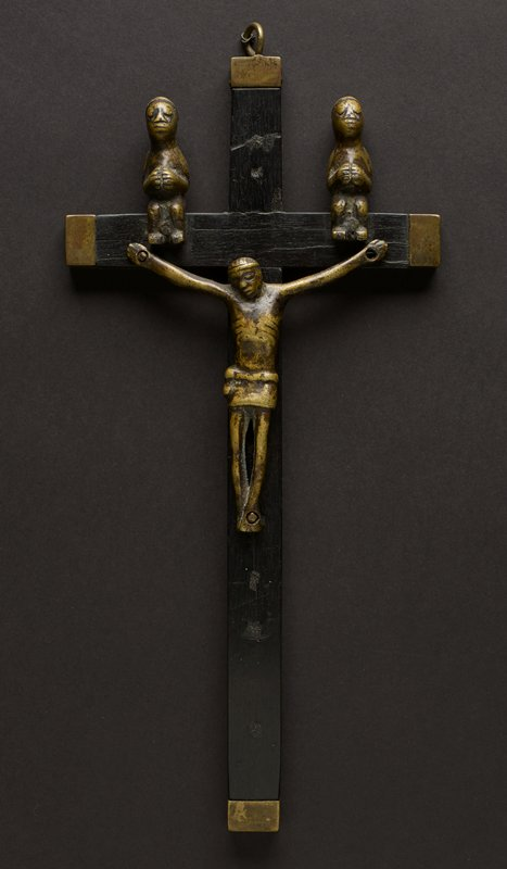 cross is a plain dark wood; tips are covered in metal; top point has a metal ring at the top; two seated figures are perched on the horizontal section on either side of the Christ figure; figures' hands are clasped together at the chest; figure of Christ has long, thin arms, nailed at the palms into the horizontal section; carved fingers on each hand; face is peaceful, with closed eyes and straight, expressionless mouth; head is rounded; torso has carved, prominent ribs on the side of the body; around waist is a carved garment; legs are long and thin; feet are nailed together; wood of the cross is dark; figures are a lighter color