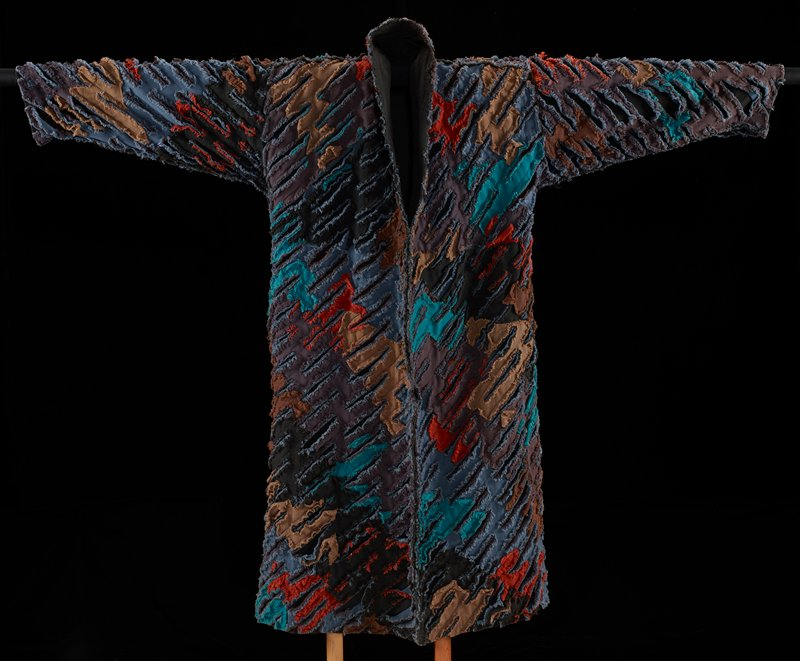 long open coat with short side slits; black with diagonal motif of appliqued irregular patches with fraying edges in brown, tan, dark orange, green and blue; diagonal stitching; black lining