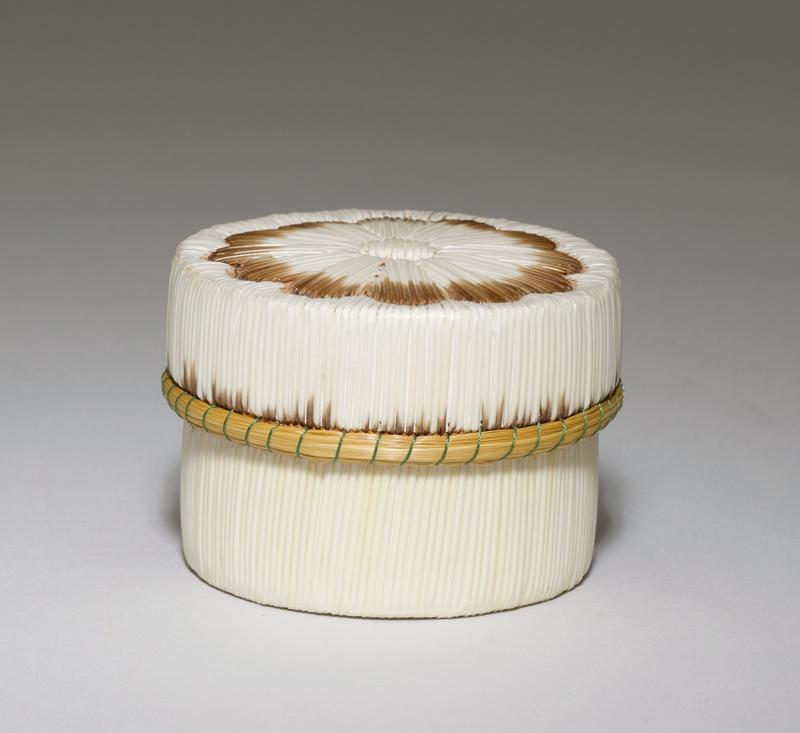 round drum shaped box with birch bark body; flat cover decorated with daisy-type floral motif in white and white with brown-tipped quills; body of box decorated with vertical white quills