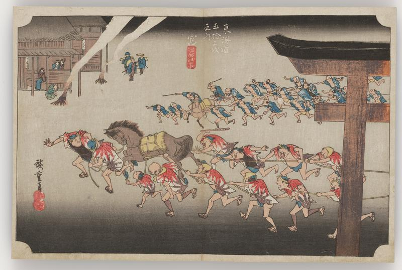 two groups of men running with ropes attached to a horse cross image field; one team is wearing red and white shirts; the other, blue and white; portion of torii gate in foreground at R; two small buildings with small bonfires and people at UL