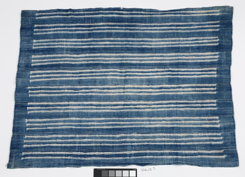 blue and white woven panel; blue dyed background with white lines and dots forming triangle and circular patterns; seven strips of fabric stitched together to form panel; two ends of panel are folded and stitched to form seam
