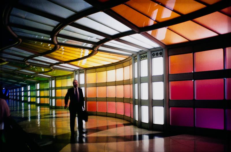 man in business suit carrying briefcase walking through a wavy tunnel constructed with brightly colored glass panels