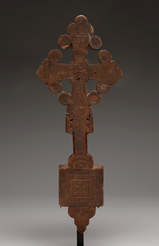 wooden cross with ornate carvings on both sides; long stem with a square base; one side of square base has smaller squares carved within base with four leaf-like patterns in center, the other side differs with more ornate carvings as well as a diamond shape in center; bottom of cross extends beyond square base and geometric carvings in ornately scalloped base; top of stem has two 'arms' protruding below cross with geometric patterns carved into them; diamond shape with carvings just above arms; cross has concave limbs with protruding buds, all caved with ornate latticework and thin lines; diamond shape carved in center of cross with four small circles in each corner