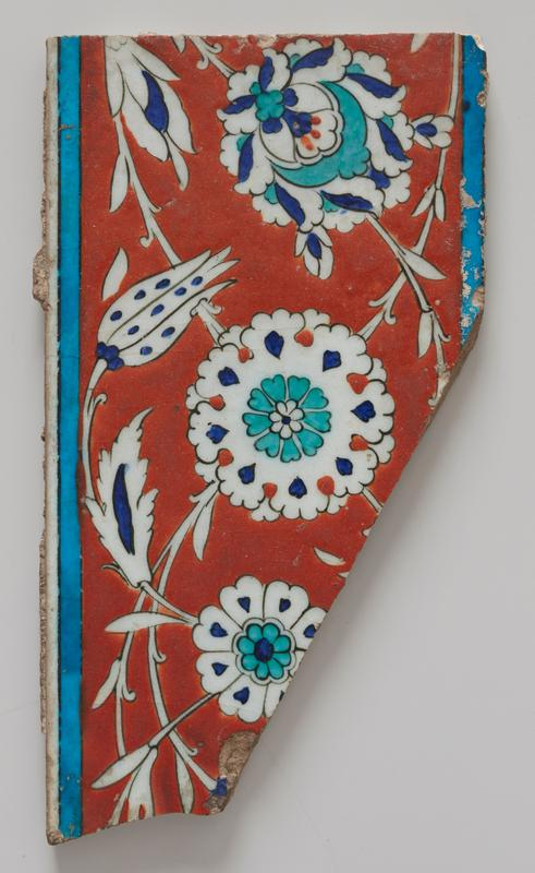 Tile palmette and tulip decoration in blue, green and white on tomato-red ground and enriched by blue band; from a border ; so called Rhodian type; corner missing.