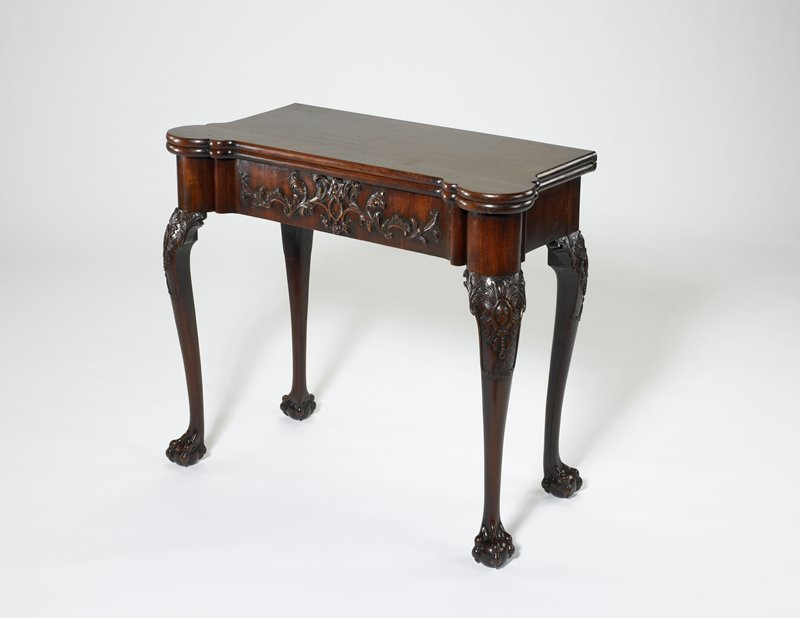 Card table; by Chippendale?, folding top with semi-circular and broken corners for placing candslesticks (?); cabriole legs terminating in claw and ball feet; knees carved with acanthus leaf designs and foliated cartouches; front of drawer with fine foliate scrollings.MIddle XVIII c. Mahogany.