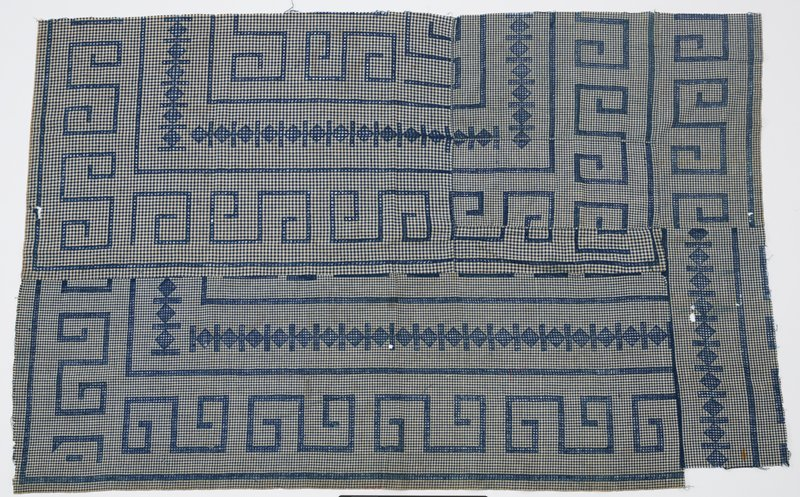 medium blue gingham with openwork designs in blue of scrolling S-shapes and squares flanked by pairs of bars; fragments of cloth stitched together