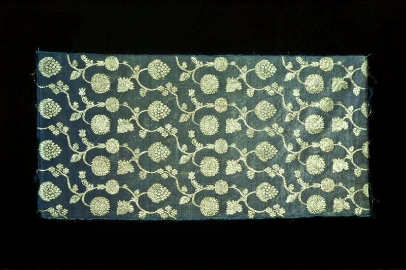 Brocade: blue satin with a silver pattern of pomegranates and grapes