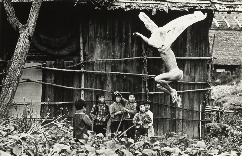 jumping man at right with garment flowing up over head, wearing a loin cloth and sandals; group of six children at center watching jumping man; foliage in foreground; building in background