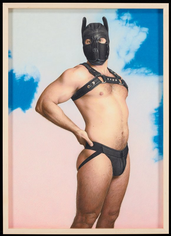 man wearing black leather mask, black leather strap across upper torso, and black underwear standing in front of non-descript space; bright blue in upper right quadrant and upper left quadrant with gradated white and pink background