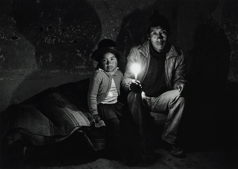 seated man and little girl; man at R wears a jacket, sweater and pants and holds a candle in his PR hand; girl at L wears a sweater and a hat