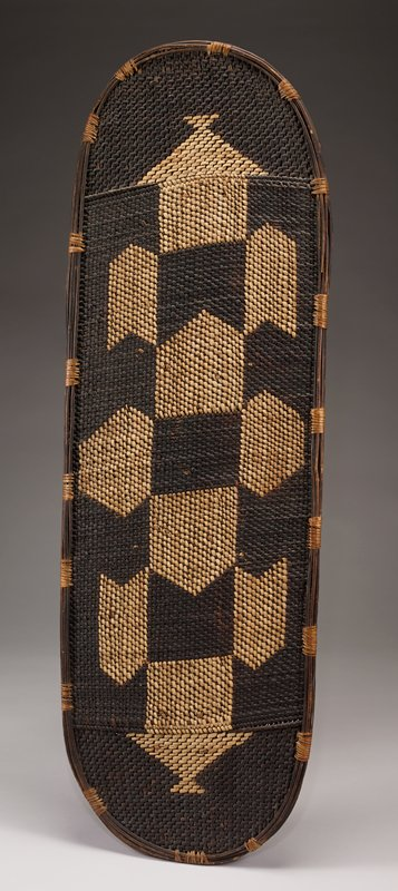 two-sided woven shield with checkered pattern in light brown and dark brown weaving; triangle shapes in light brown on either end; long wooden handle on backside; alternating bands of weaving around outer edge