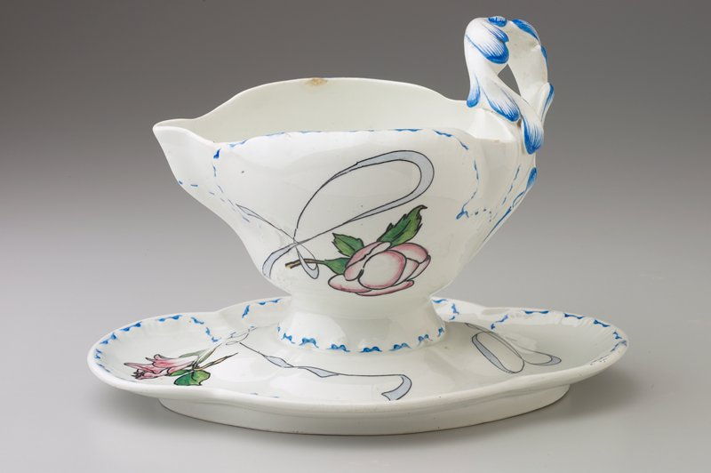 cup-shaped bowl with looped handle; bowl attached to oval saucer; faience decoration of red flowers and blue scrolls; blue trim