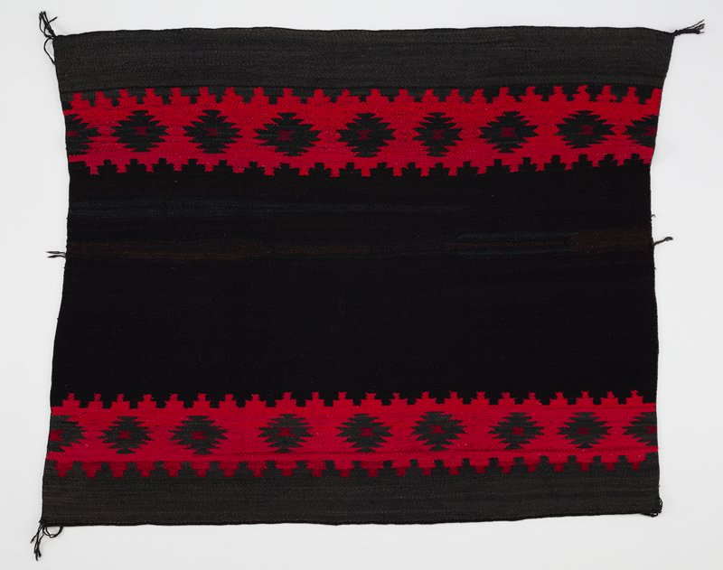 dark background with two horizontal red bands with zigzagging lines; black ikat designs within red bands with red hourglass motifs inside; central block is black; borders are dark charcoal gray