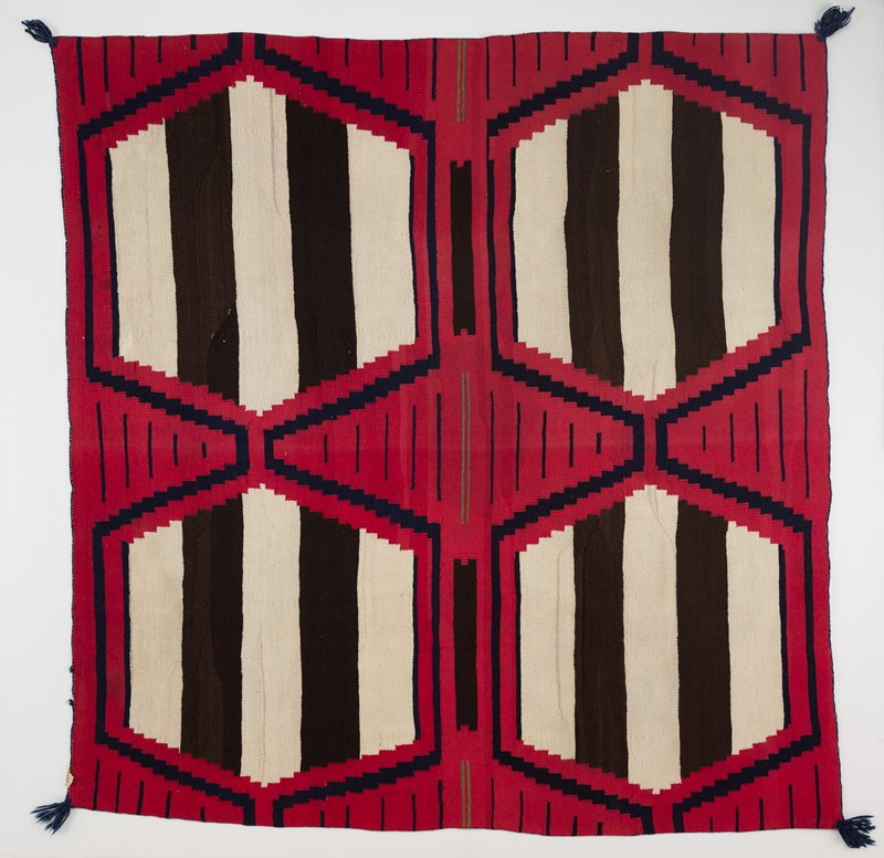 red wool panel with thin blue stripes on outer edges and in center; thin green bands along the side edges and in the center with thick brown bands in between; four hexagon shapes in cream and brown bands of dye in all four quadrants; staggered bands of blue color surround hexagon shapes; blue threaded band around outer edge; blue fringe in all four corners; small cloth tag sewn in corner; has a Velcro heading band