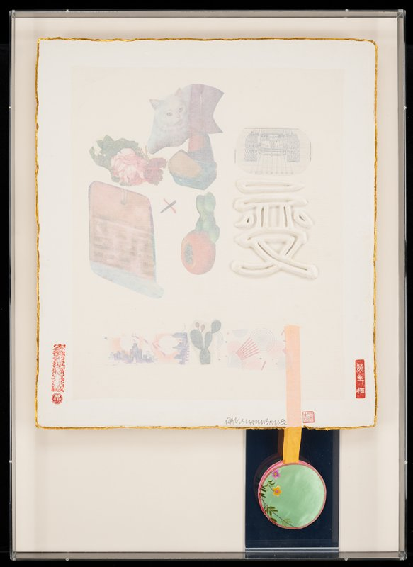 paper collage with muted color elements; raised Asian character at right center; collage elements include images of a white cat, red and pink flowers, cactus, cartoonish city skyline, prayer board, diagram of a machine; red seals/stamps in lower corners and bottom right; orange ribbon attached in LRQ with a round green silk fabric element with embroidered flowers hanging in front of a mirror, with pink backing of round element visible in mirror; gold leaf edging; inside a Plexi box