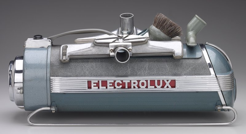 tube-shaped blue, grey and chrome vacuum with tan tube and attachments that snap onto handle
