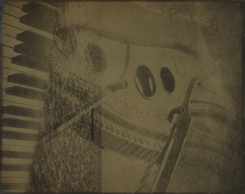 hazy image of a piano with abstract ripples of water running vertically down the left side