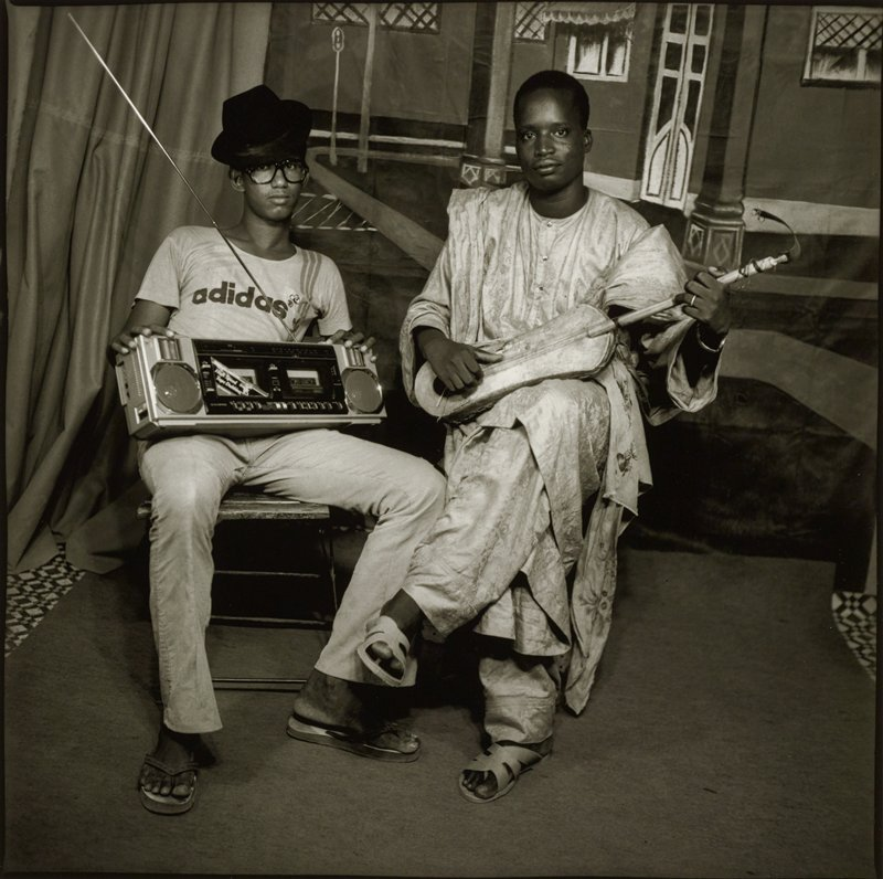 two seated men; younger man on left wearing glasses, hat, Adidas t-shirt, pants and flip-flop shoes, holding a boom box on his lap; man on right holding a stringed instrument with a lozenge-shaped body on his lap, wearing matching garments (pants, long shirt, jacket) with brocade pattern and sandals; painted backdrop with buildings on a street