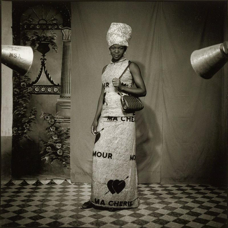 "standing black woman wearing a long skirt and a sleeveless blouse made of the same fabric printed with double hearts pierced with an arrow and the words, ""AMOUR"" and ""MA CHERIE""; woman also wear gold hoop earrings and a printed headwrap and carries a purse with a diamond design; checked floor; cloth backdrop with a painted backdrop of column and flowers at left"